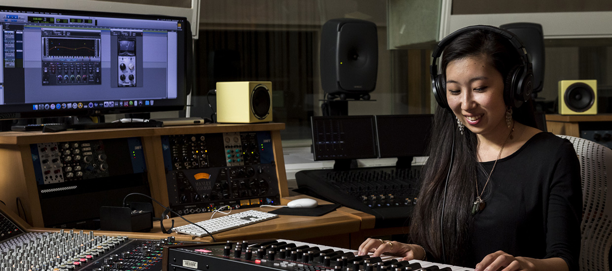 A woman wearing a black shirt practices piano while wearing headphones in a music engineering studio.