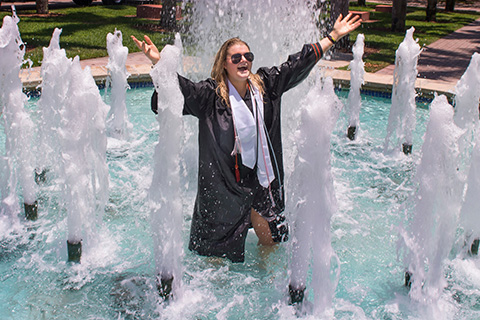 Student celebrating graduation in a fountain