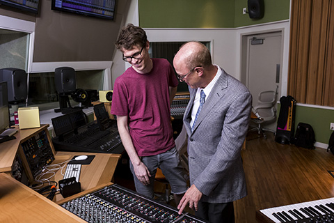 Teacher and student looking over a mixing console