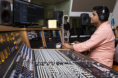 Music Engineering sitting at a mixing console